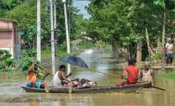 Flood-affected villagers use a boat to take a...- India TV Paisa