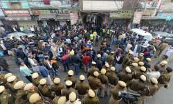 Police personnel and onlookers stand near a factory at...- India TV Paisa