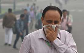 A pedestrian covers his face with a handkerchief...- India TV