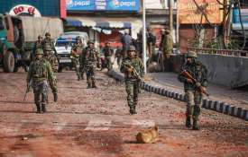 Army personnel patrol a street during a...- India TV