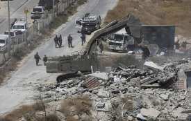 Israeli forces destroy a building in a...- India TV