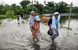People wade through a flooded road following the incessant monsoon rainfalls at Kalgachi, in Barpeta- India TV