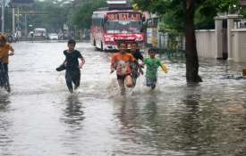 Children play at a waterogged road following heavy monsoon rain in Varanasi- India TV