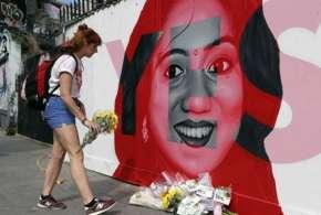 A woman places flowers by a mural showing Savita Halappanavar | AP Photo- Khabar IndiaTV