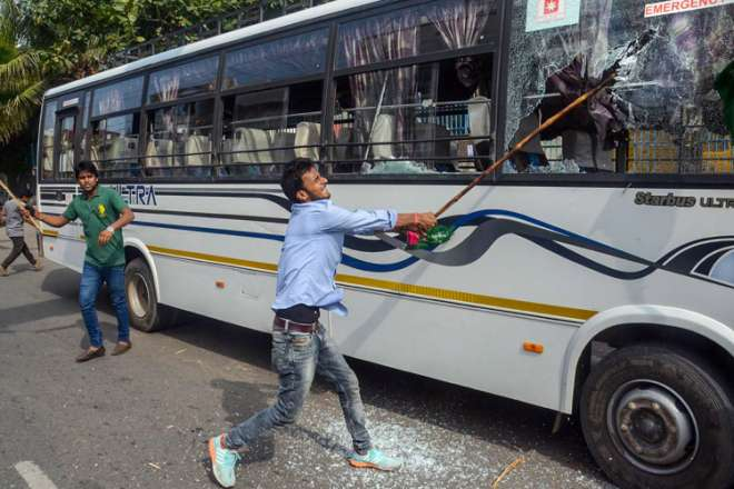Jan Adhikar Party supporter vandalises vehicles during 'Bharat Bandh' protest against fuel price hike and depreciation of the rupee, in Patna