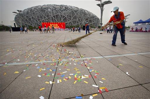 2022 विंटर ओलंपिक की दावेदारी मिलने पर जश्न के लिए लोग इकट्ठा हुए। लोगों के वहां से जाने के बाद वहां सफाई करता एक कर्मी।