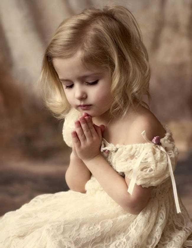 प्रार्थना करती हुई बच्ची।