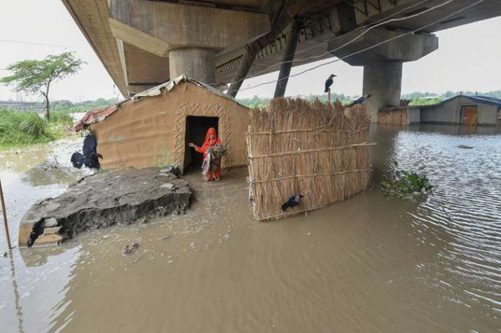 A woman stands outside her submerged shanty at Yamuna Khadar, as the water level of Yamuna river rises in New Delhi