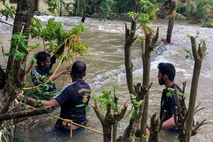 Navy personnel along with volunteers rescue people who were trapped in the flood-hit areas in Thrissur district