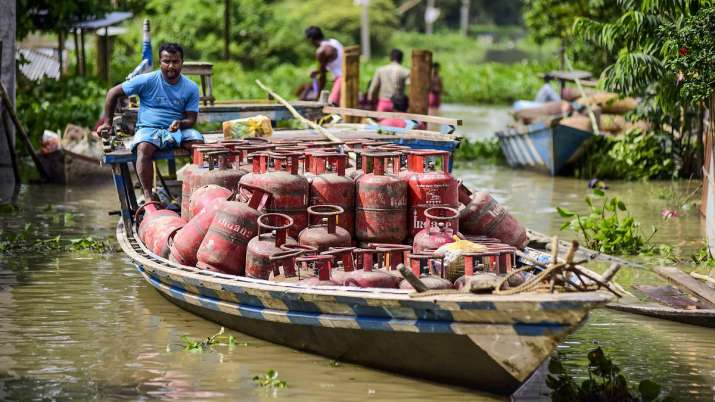 A flood-affected villager moves LPG cylinders loaded on a boat to a safer place, in Morigaon.