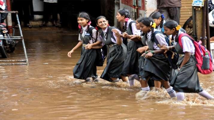 पश्चिम बंगाल के हुबली में बाढ़ के पानी के बीच स्कूल जाती छात्राएं