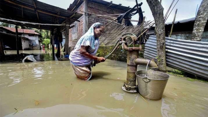 असम के कामरूप में हैंड पंप से पानी भरती महिला