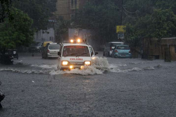An ambulance makes way through a flooded road after...- India TV
