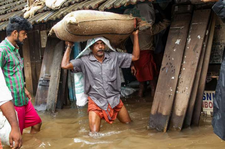 A person carries a grain sack as his house gets flooded...- India TV