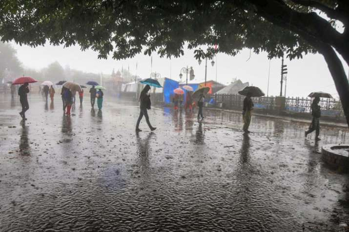 People protect themselves with umbrellas during heavy...- India TV