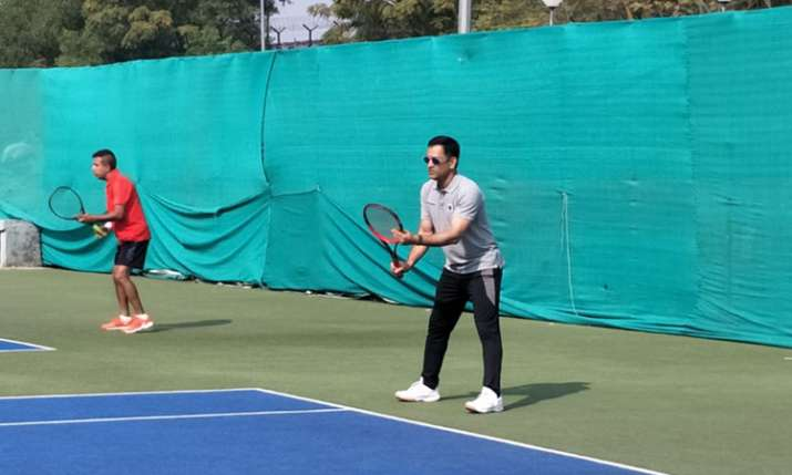 क्रिकेट का बल्ला नहीं टेनिस रैकेट लेकर मैदान पर उतरे एमएस धोनी, देखें तस्वीरें- India TV