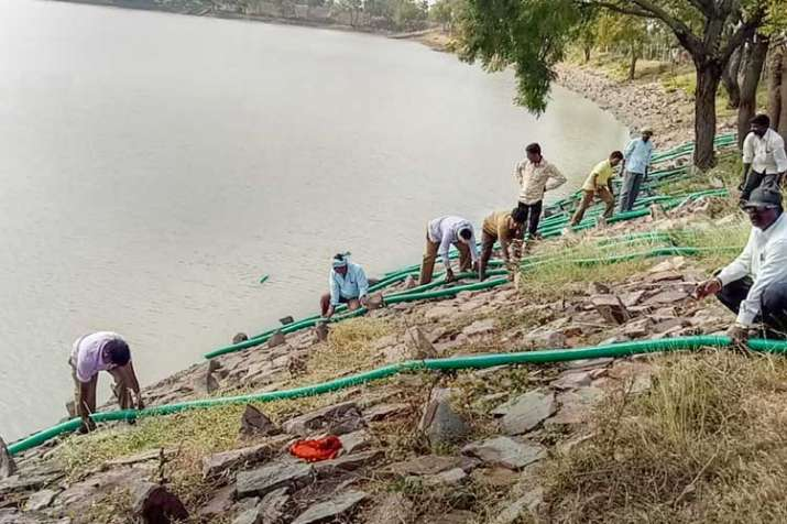 Administration employees drain water from the 36-acre...- India TV