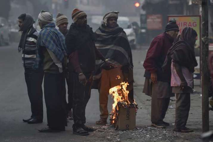 People gather around a makeshift bonfire to warm...- India TV