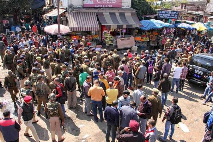 Police personnel inspect the site after a powerful...- India TV