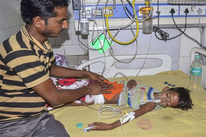 A man takes care of a child suffering from Acute Encephalitis Syndrome (AES) at a hospital in Muzaff- India TV