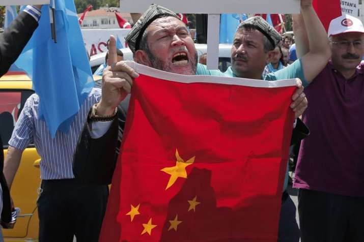 Uighurs living in Turkey and Turkish supporters, chant slogans as they hold a Chinese flag | AP File- India TV