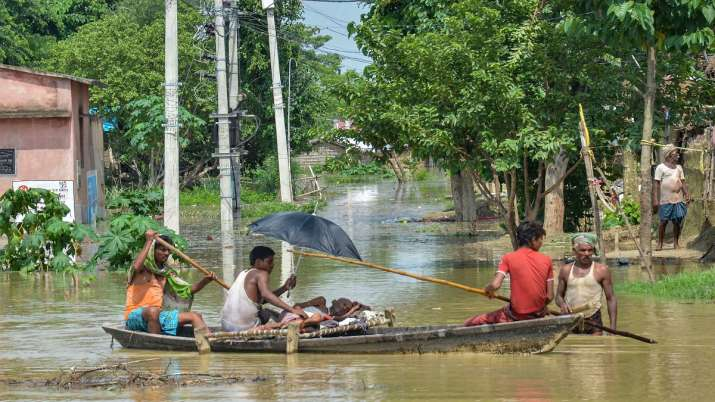 Flood-affected villagers use a boat to take a patient to...- India TV