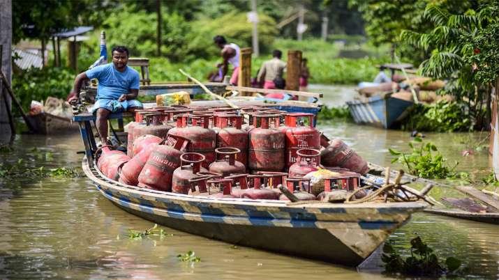 असम के मोरीगांव में बाढ़ के बीच एलपीजी सिलेंडर पहुंचाने की कोशिश