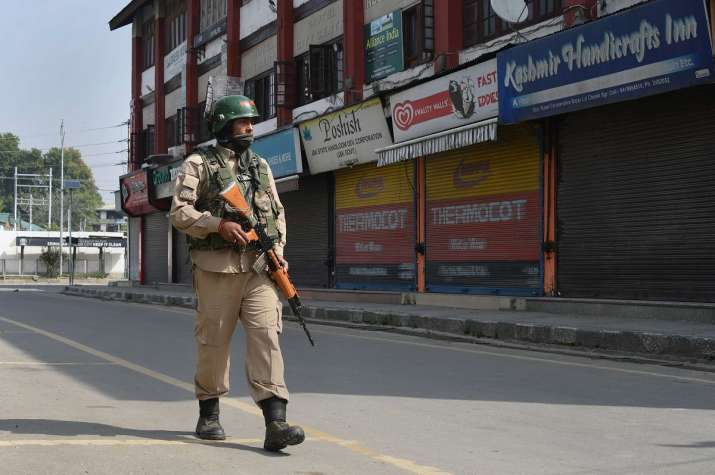 A security personnel patrols a street during...- India TV