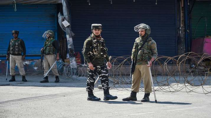 Security personnel stand guard during restrictions in Srinagar.- India TV