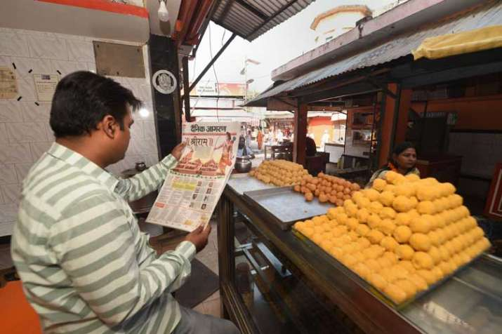 Shopkeeper reads newspaper fronted with headlines on...- India TV