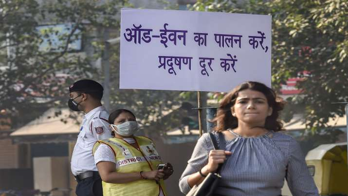 Civil Defence volunteer wearing a mask displays a placard asking people to obey the odd-even rule, i- India TV Paisa