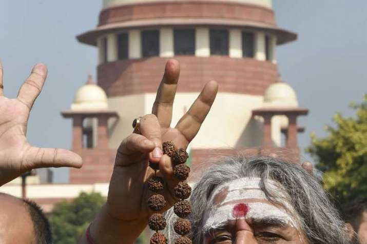A sadhu flashes the victory sign at the Supreme Court...- India TV