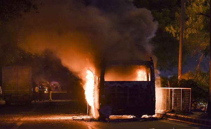 A bus set ablaze by protestors against the...- India TV